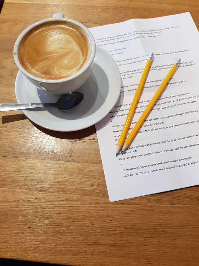 A cappuccino, a typescript and two pencils